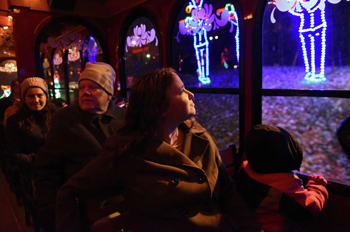 Martha Goldstein of Schenectady, second from right, takes a trolly ride through the lights with her daughter Ariel, 5, right, after Mayor Kathy Sheehan threw the switch to open the 22nd Annual Price Chopper/Market 32 Capital Holiday Lights in the Park in Washington Park on Thursday, Nov. 15, 2018 in Albany, N.Y. The Holiday Lights is produced by the Albany Police Athletic League. The drive-through begins nightly on Friday, November 23, 2018 through January 2, 2019. (Lori Van Buren/Times Union)