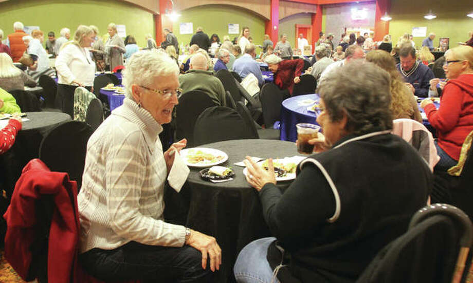 Pat Stewart, left, of Godfrey, and Rita Ford, of East Alton, talk while eating at Taste of Downtown, an annual fundraiser for Alton Main Street held Thursday in the Music Hall at the Argosy Casino Alton. About 400 people sampled everything from candies to crab cakes from 18 different restaurants, bars and others. Photo: Scott Cousins | The Telegraph