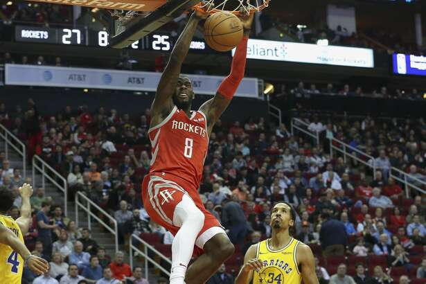 Houston Rockets forward James Ennis III (8) scores a slam dunk over Golden State Warriors players Quinn Cook (4) and Shaun Livingston (34) during the second quarter of the NBA game against the Golden State Warriors at Toyota Center on Thursday, Nov. 15, 2018, in Houston.