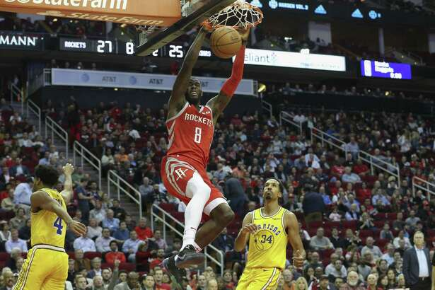 Rockets forward James Ennis III, left, announces his presence to Shaun Livingston and the reigning NBA champion Warriors with a slam dunk in the second quarter Thursday night at Toyota Center.