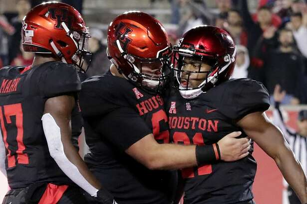 Houston running back Patrick Carr, right, gets congrats after his touchdown from Terry Mark (17) and lineman Will Noble, middle, during the first half of their football game against Tulane Thursday, Nov. 15, 2018 in Houston, TX.