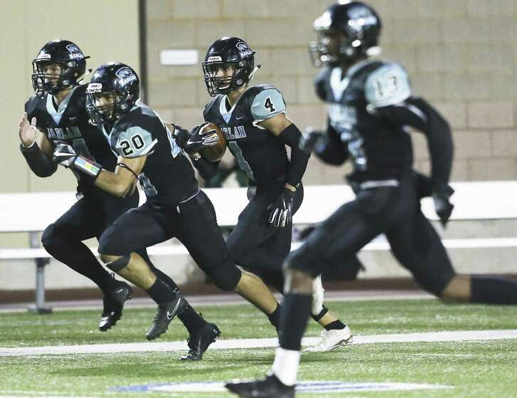 Harlan defensive back Jacob Garcia gets behind blockers after picking off a bobbled pass. His long return set up a quick touchdown in the Hawks' 33-14 first-round win over Sam Houston.