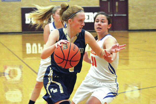 Father McGivney sophomore Anna McKee drives to the basket during the first quarter of Thursday's game against Roxana in the semifinals of the Dupo Cat Classic.