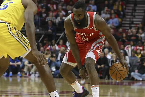 Houston Rockets guard James Harden (13) dribbles while Golden State Warriors center Damian Jones (15) is defensing during the first quarter of the NBA game at Toyota Center on Thursday, Nov. 15, 2018, in Houston.