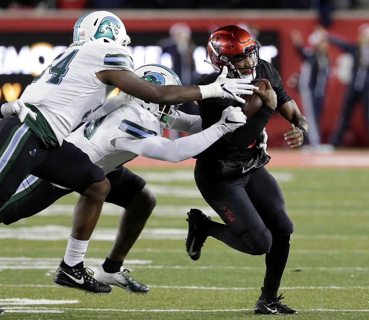 Tulane defensive end Carlos Hatcher, left, and linebacker Marvin Moody, middle, catch Houston quarterback D'Eriq King, right, on a keeper play during the first half of their football game Thursday, Nov. 15, 2018 in Houston, TX.