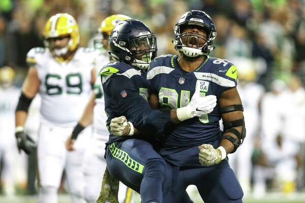 Seahawks defensive lineman Frank Clark (left) hugs Seahawks defensive lineman Rasheem Green as Green celebrates his key sack of Packers quarterback Aaron Rodgers during the fourth quarter of Seattle's game against Green Bay, Thursday, Nov. 15, 2018, at CenturyLink Field.