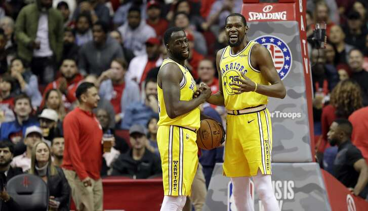 Golden State Warriors' Kevin Durant (35) talks with Draymond Green after a turnover during the second half of an NBA basketball game against the Houston Rockets Thursday, Nov. 15, 2018, in Houston. (AP Photo/David J. Phillip)