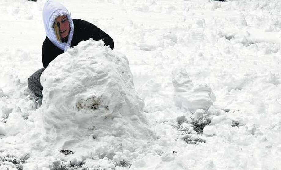 Illinois College freshman Delani Dillard works on the base of a snowman Thursday on IC's campus after more than 6 inches of snow fell overnight. Photo: Samantha McDaniel-Ogletree | Journal-Courier