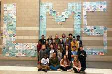 """Students pose in front of Liberty Middle School's """"LMS"""" sign as proud Diversity Club members."""