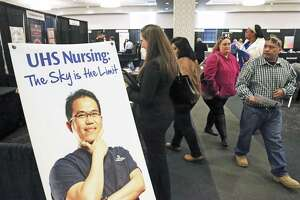 Applicants walk near the University Health System table Tuesday during the Mega Career Fair at the Norris Conference Center.
