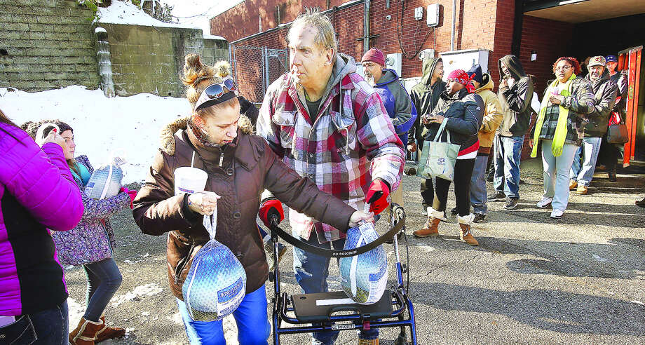 A woman, and a man with a walker, walk away after each picked up their free frozen turkey Friday behind the Alton Salvation Army on Alby Street. About 500 turkeys were handed out courtesy of the TorHoerman Law in Edwardsville. Photo: John Badman | The Telegraph