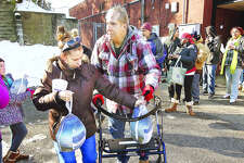 A woman, and a man with a walker, walk away after each picked up their free frozen turkey Friday behind the Alton Salvation Army on Alby Street. About 500 turkeys were handed out courtesy of the TorHoerman Law in Edwardsville.