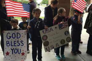 Members of Cub Scout Pack 343 of Katy Mia Moreno and Lexi Manderfeld brought a sign and flags to greet the new enlistees Sunday at Second Baptist Church-West Campus.