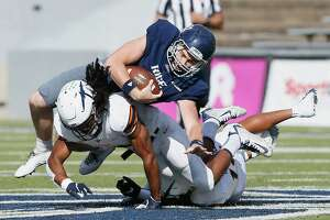 HOUSTON, TX - NOVEMBER 03:  Austin Walter #2 of the Rice Owls is tackled by Jerrell Brown #18 of the UTEP Miners and Tyson Wilson #14 in the second quarter on November 3, 2018 in Houston, Texas.
