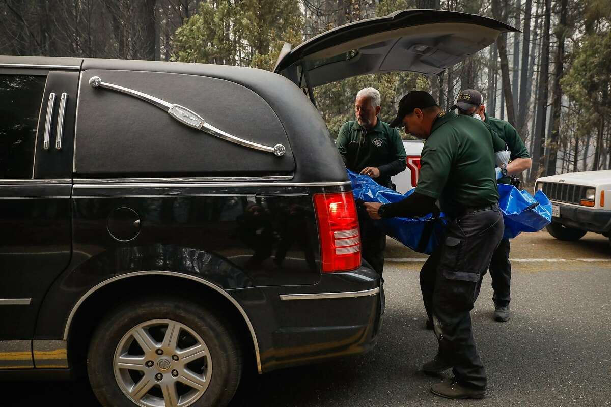 Butte County investigators transport a body bag into a hearse after recovering remains from a destroyed property following the Camp Fire in Magalia, California, on Thursday, Nov. 15, 2018.