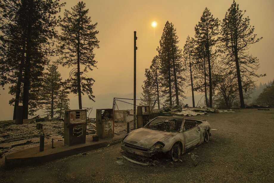 As the Camp Fire burns nearby, a scorched car rests by gas pumps near Pulga in Butte County. Photo: Noah Berger / Associated Press