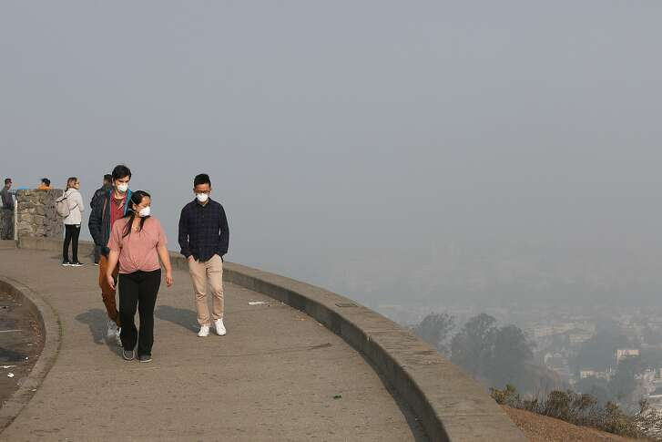"""Jack Fatheree (l to r) of Texas, Nia Blas of San Francisco and Derek Chan of Iowa wear masks as they take in a hazy view of San Francisco from Twin Peaks as Blas shows her friends around the city on Friday, November 16, 2018 in San Francisco, Calif.  The Bay Area continued to register """"very unhealthy"""" levels of particulate matter throughout the region Friday morning,"""