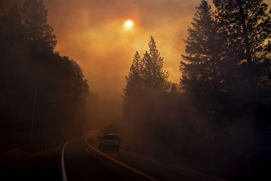 A vehicle drives through smoke from a wildfire near Pulga (Butte County). Photo: Noah Berger / Associated Press