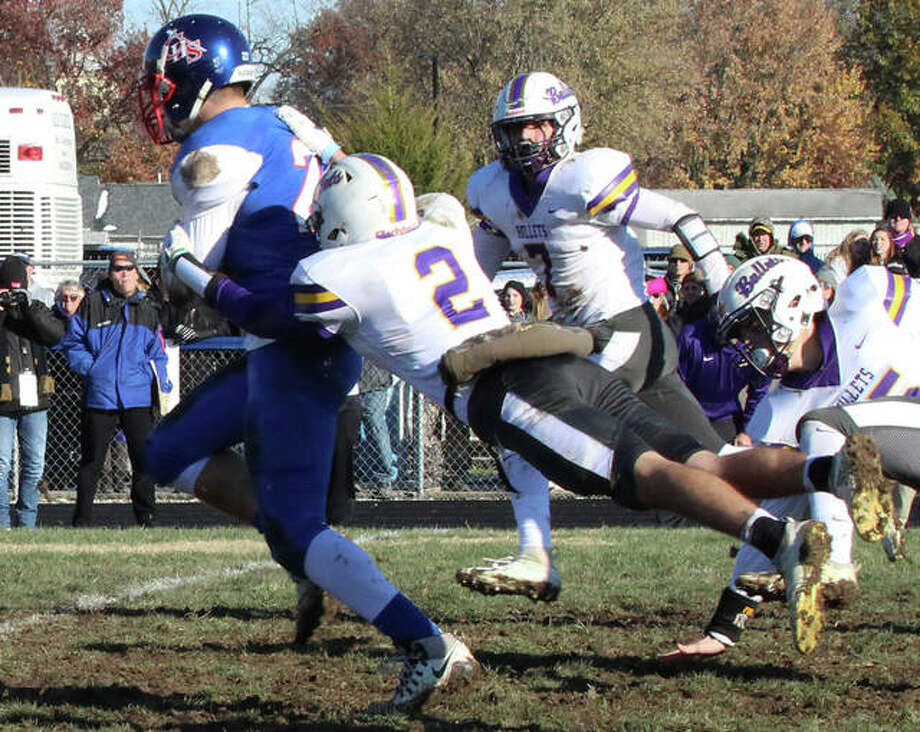 Williamsville's Cameron Witts (2) hangs on until help arrives for the Bullets to take down Carlinville receiver Jake Ambuel in last Saturday's Class 3A quarterfinal football game in Carlinville. Ambuel had 12 catches in the Cavs' 35-21 victory. Carlinville (12-0) will play in the 3A semifinals at 2 p.m. Saturday at 12-0 Monticello. Photo: Greg Shashack / The Telegraph