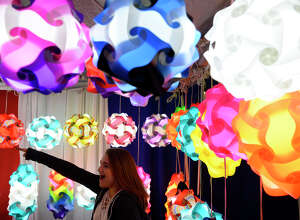 Charyti Touchet looks at colorful lamps for sale at a booth in the vendor hall at the YMBL South Texas State Fair on Friday night.  Photo taken Friday 3/23/18 Ryan Pelham/The Enterprise