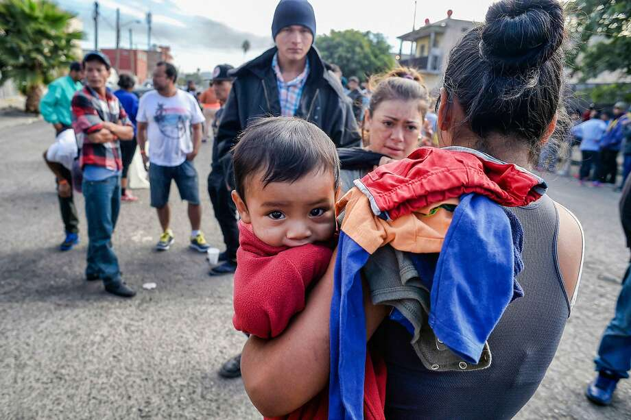 Central American migrants - mostly Hondurans - moving toward the United States in hopes of a better life, line up for food at a shelter in Playas de Tijuana, Mexico, on November 15, 2018. The Central American migrant caravan converged on the US-Mexican border Thursday after more than a month on the road, undeterred by President Donald Trump's deployment of thousands of American troops near the border. (ALFREDO ESTRELLA/AFP/Getty Images) Photo: Alfredo Estrella / AFP / Getty Images