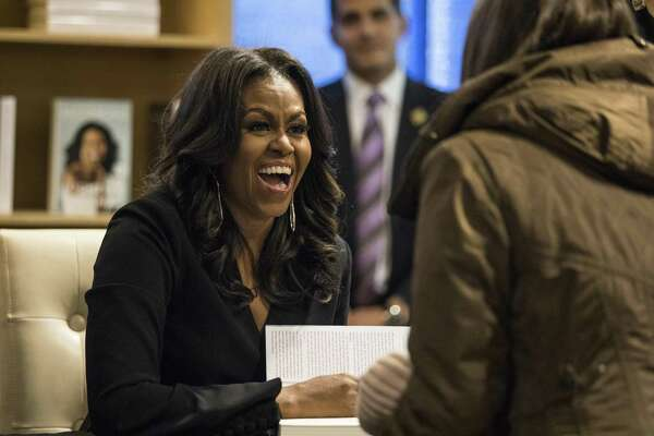 """Former first lady Michelle Obama signs copies of her new book """"Becoming"""" and greets fans as she kicks off a national book tour at Seminary Co-op Bookstore in Chicago."""