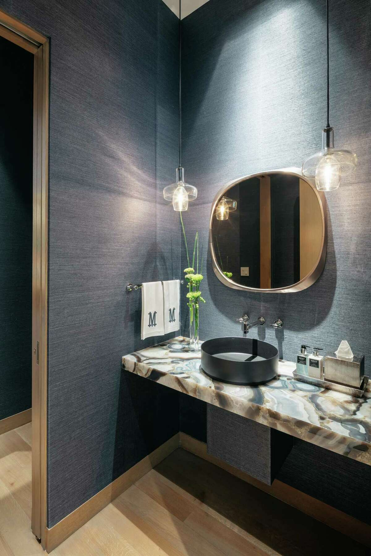 Dark blue grasscloth wallpaper complements the gray-white movement in the agate counter in the powder bathroom.