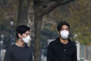 York Wang (left) and Chris Ko wear breathing masks while walking theough Sproul Plaza at UC Berkeley on Friday, Nov. 16, 2018. Ko says heÕs already sick, so trying to avoid the bad air is really difficult. University officials cancelled classes Friday because of the unhealthy air conditions which continue to choke the Bay Area with heavy smoke from the Camp Fire in Butte County.