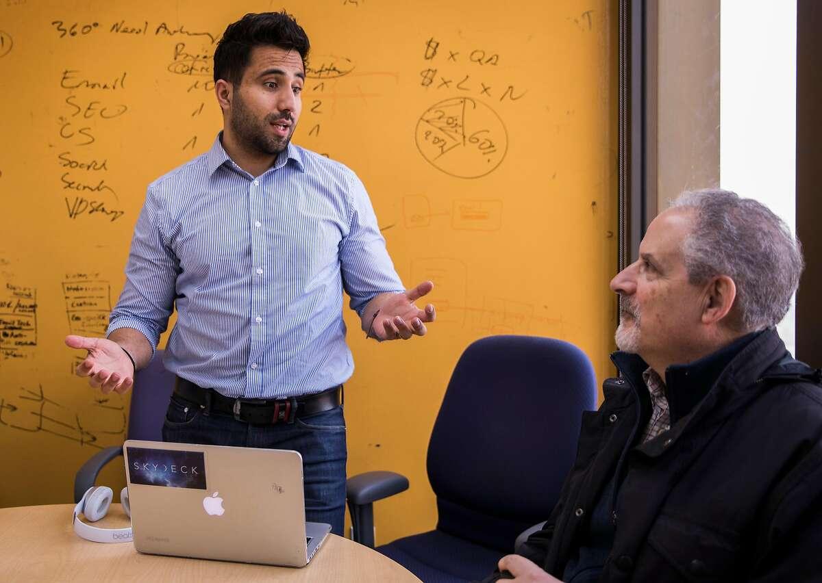 Predictim CEO Sal Parsa talks with key advisor Bill Schneiderman during a team meeting at SkyDeck in Berkeley, Calif. Thursday, Nov. 15, 2018.