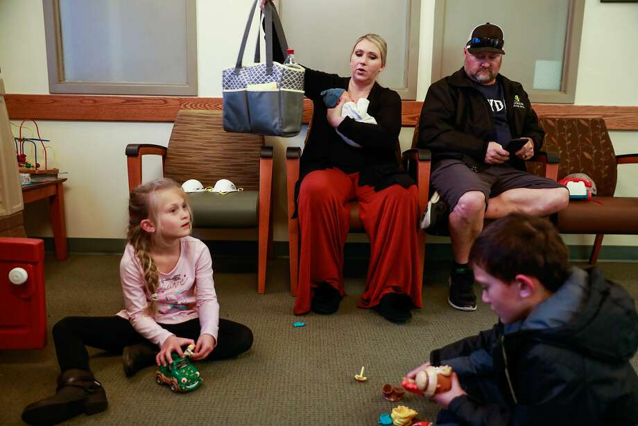 Rachelle Sanders holds her son Lincoln, born just hours before the Camp Fire roared through Paradise. She and husband Chris, and her children Aubrey Zuccolillo, 7, and Vincent Zuccolillo, 9, wait at a medical center in Chico days after fleeing the fire. They lost their home. Photo: Gabrielle Lurie / The Chronicle