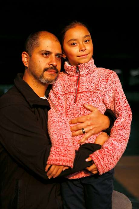 Jamie Mansanares and daughter Tezzrah, 7, ran from flames after he helped evacuate elderly patients from a care home. Photo: Santiago Mejia / The Chronicle