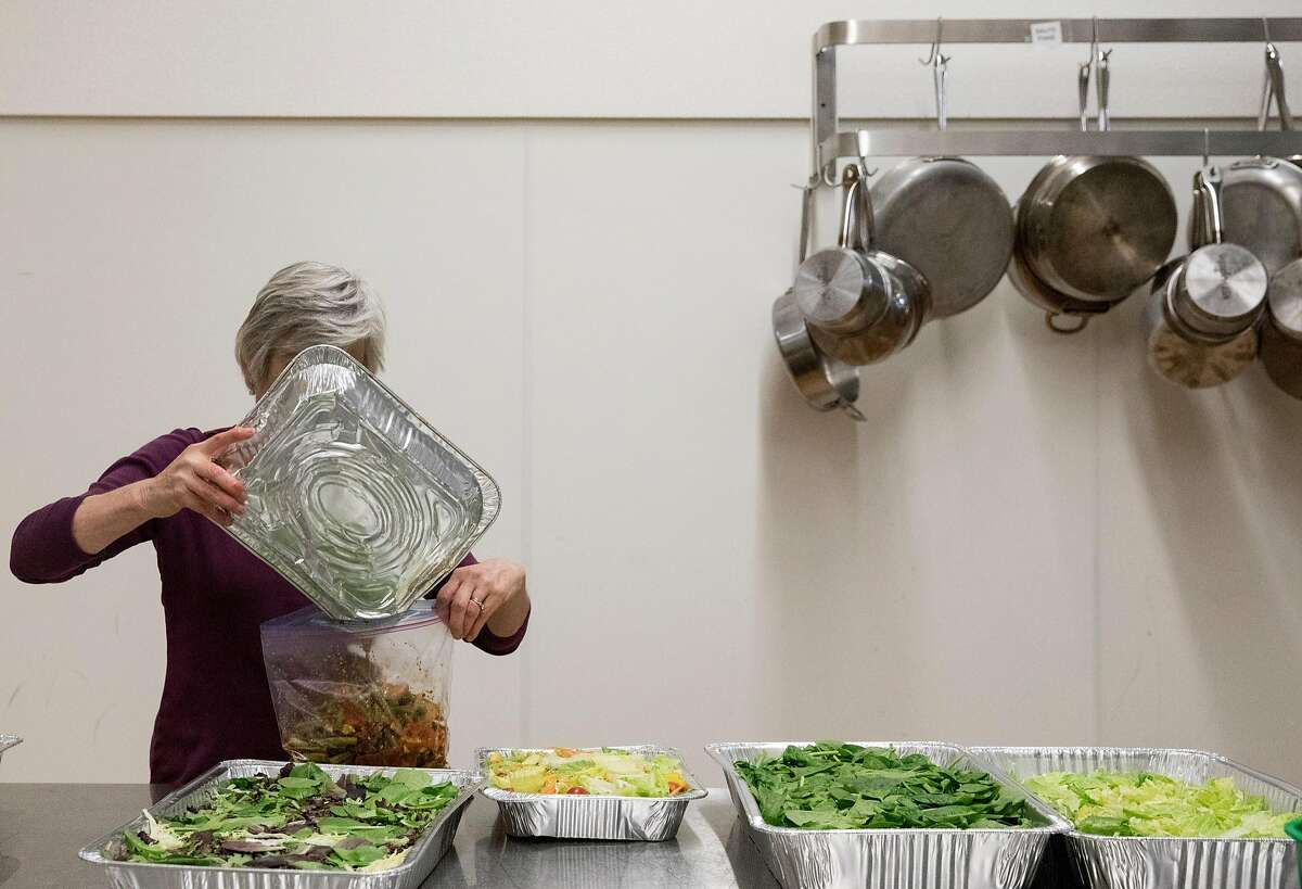 Berkeley Food Network board member Susan Choy repackages food leftover from a local restaurant to be stored and given to homeless shelters while working at Bauman College in Berkeley, Calif. Thursday, Nov. 15, 2018.