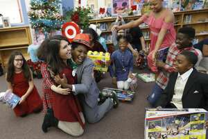 Ten-year-old Kevin Stennett hugs Target representative Britney Fontenot as he and his fellow fifth-grade students at Longfellow Elementary School react after being told they could keep toys from Target after they  announced the top 10 toys for children this holiday season based on the results of surveys they conducted. Friday, Nov. 16, 2018, in Houston. This year marks the ninth consecutive year that sudents have conducted the survey with other students at the school.  Students also showcase samples of the toys, which were donated by Target.