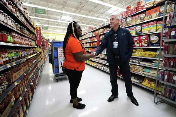 Walmart U.S. President and CEO Greg Foran, right, shakes hands with associate Alicia Carter as she fulfills online grocery orders at a Walmart Supercenter Friday, Nov. 9, 2018, in Houston. (AP Photo/David J. Phillip)