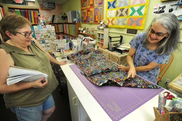 Owner Jane Helfgott cuts fabric for customer Debbie Talmadge, left, of Woodbury, at The Bolt Quilt Shop at 150 Main Street in Monroe, Conn. on Thursday, September 8, 2016. Helfgott is one of many small business owners concerned over the announcement that a Super Wal-Mart is being constructed nearby.