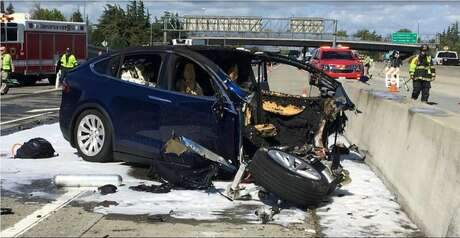 "FILE - In this March 23, 2018 file photo provided by KTVU, emergency personnel work a the scene where a Tesla electric SUV crashed into a barrier on U.S. Highway 101 in Mountain View, Calif. The test results by AAA released Thursday, Nov. 15, 2018, come after several highly publicized crashes involving Tesla vehicles that were operating on the company's system named ""Autopilot."" The National Transportation Safety Board is investigating some of the crashes, including the March fatality that involved a Model X that struck a freeway barrier. (KTVU via AP, File)"