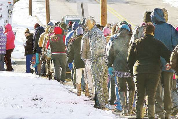 A large crowd lined up Friday morning in front of the Alton Salvation Army in the 500 block of Alby Street for the TorHoerman Law Firm's annual turkey giveaway. People started lining up for the event two hours ahead of time. The Edwardsville firm had 500 turkeys to give away this year.