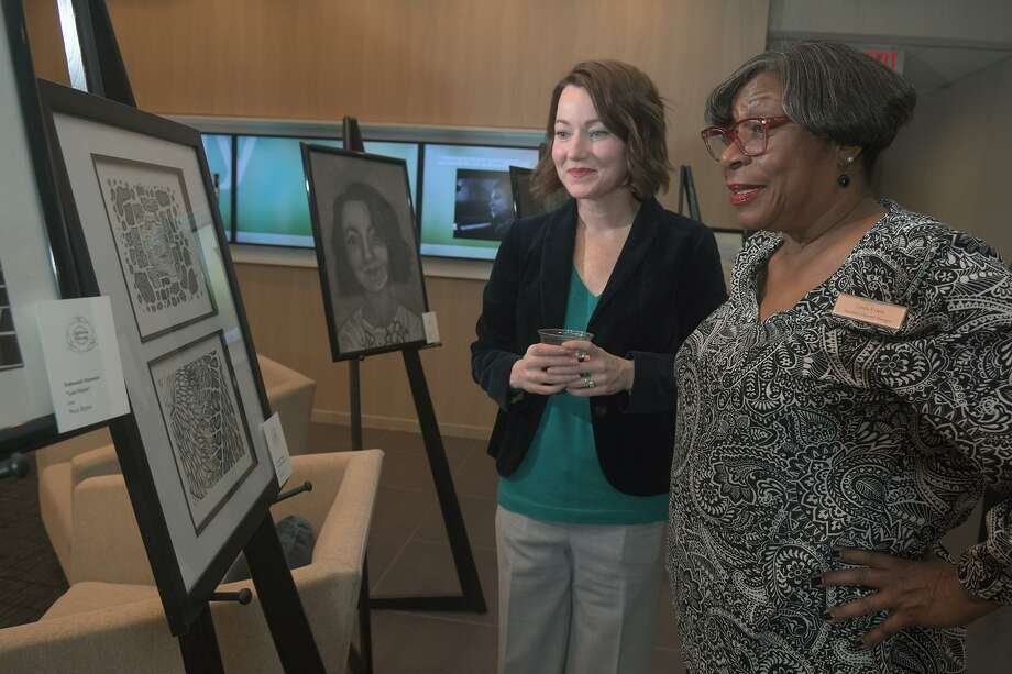 """Stephaney Kennedy, 36, left, from Houston and a Graphic Design student at Lone Star College - University Park, shows off her ink piece entitled """"Pattern Progressions"""" to Linda Evans, Asst. Gen. Mgr. of Springhill Suites by Marriott Houston Northwest during the """"Art Night 2018"""" celebration hosted by the hotel and held to raise funds for the purchase of underfunded schools on Nov, 15, 2018. Photo: Jerry Baker, Houston Chronicle / Contributor / Houston Chronicle"""