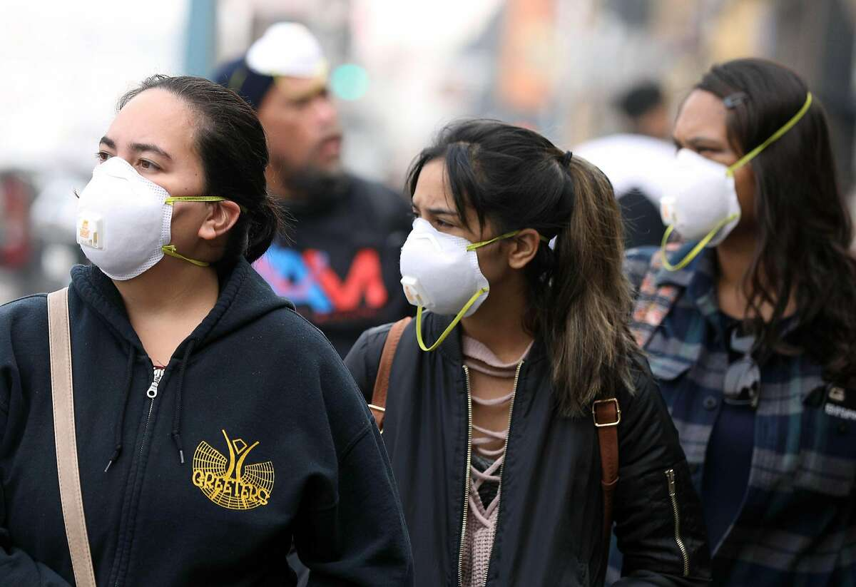 """Kelsey Kahaleauki (fore ground l to r) Taira Kahaleauki and Pua Kaholokula, all of Hawaii wear masks as they walk on Jefferson Street with other family members in Fisherman's Wharf on Friday, November 16, 2018 in San Francisco, Calif. The Bay Area continued to register """"very unhealthy"""" levels of particulate matter throughout the region Friday morning,"""