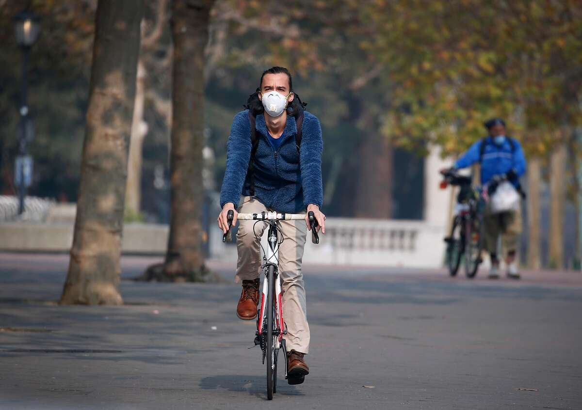 A man wears a breathing mask while bicycling through Sproul Plaza at UC Berkeley on Friday, Nov. 16, 2018. University officials cancelled classes Friday because of the unhealthy air conditions which continue to choke the Bay Area with heavy smoke from the Camp Fire in Butte County.