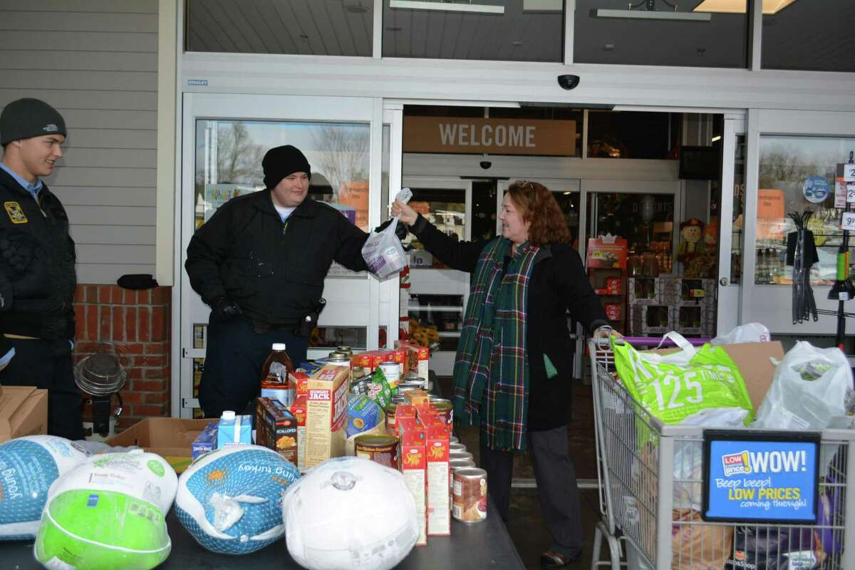State Police Cadets, Nick Sordi, left and Robert Lay, accept a donation from a local shopper in Litchfield