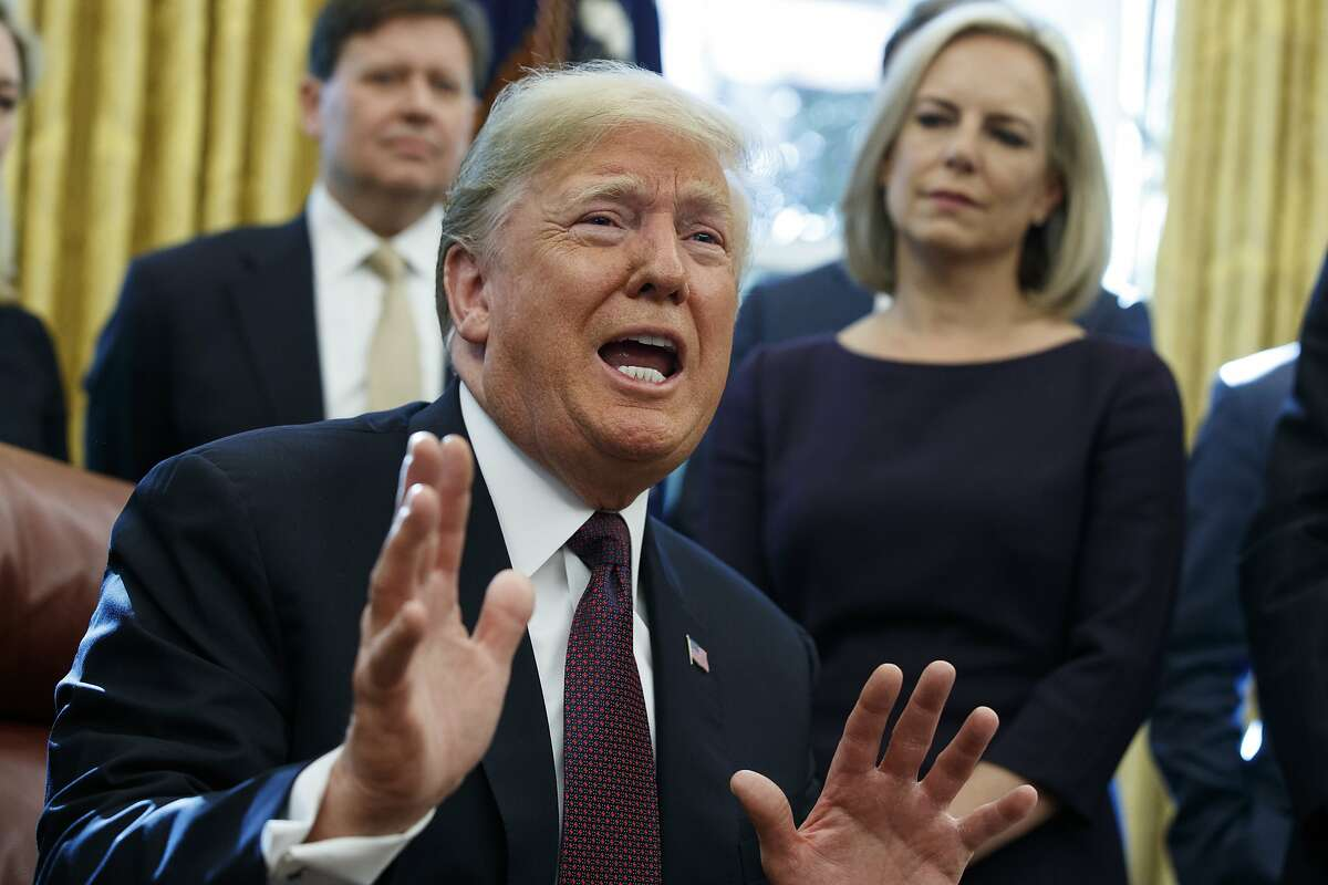 """President Donald Trump answers a reporters question about the investigation of special counsel Robert Mueller during a signing ceremony of the """"Cybersecurity and Infrastructure Security Agency Act,"""" in the Oval Office of the White House, Friday, Nov. 16, 2018, in Washington. (AP Photo/Evan Vucci)"""