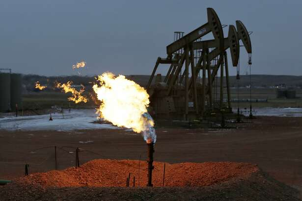 FILE - In this Dec. 17, 2014, file photo, oil pump jacks work behind a natural gas flare near Watford City, N.D. As drivers, shippers and airlines continue to enjoy lower fuel prices, the oil industry is wrestling with layoffs and losses. (AP Photo/Eric Gay, File)