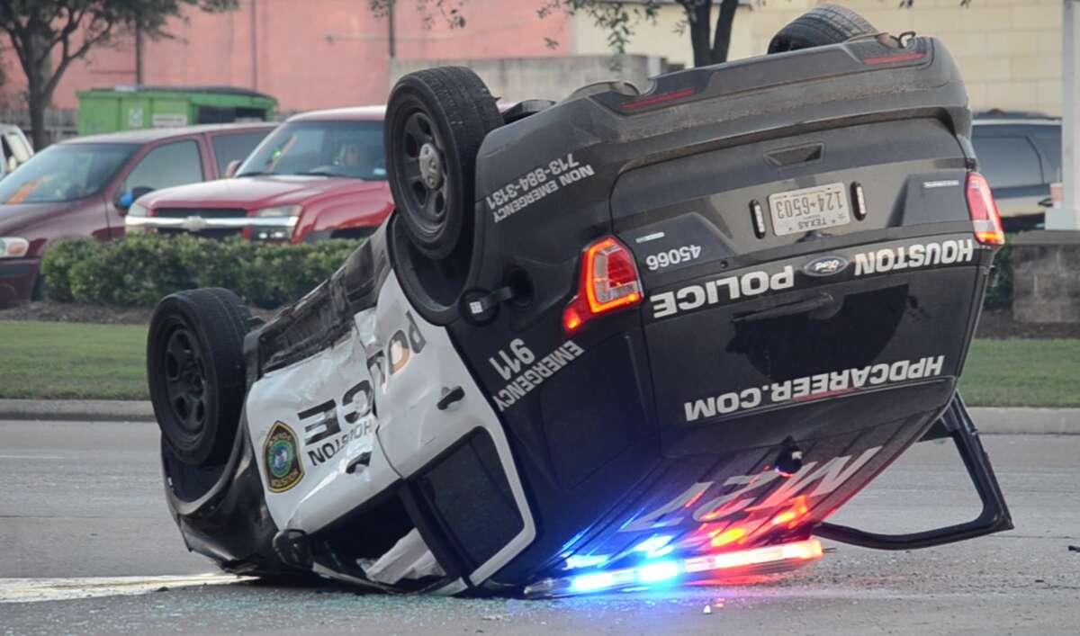 Houston police officers investigate a crash where an officer's SUV flipped along the East Freeway frontage road at Wayside Drive on Friday, Nov. 16, 2018.