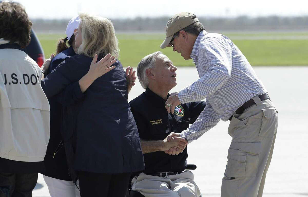 Texas Gov. Greg Abbott, center, greets Energy Secretary Rick Perry, right, as they prepare to visit areas affected by Hurricane Harvey, Thursday, Aug. 31, 2017, in Corpus Christi, Texas. (AP Photo/Eric Gay)