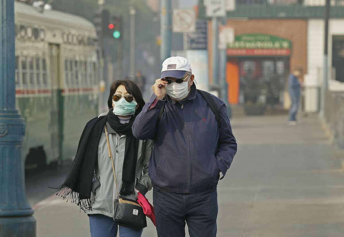 A couple wears masks while walking at Fisherman's Wharf through smoke and haze from wildfires Friday, Nov. 16, 2018, in San Francisco. (AP Photo/Eric Risberg)