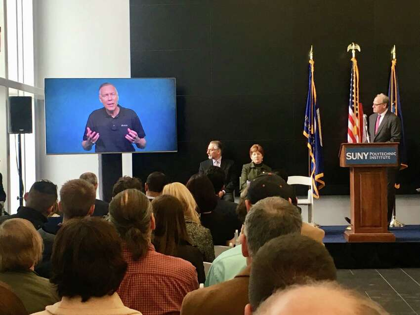 Applied Materials CEO Gary Dickerson appears via video during a press conference on Nov. 15, 2018 at SUNY Polytechnic Instutute's ZEN Building. Applied Materials is planning to fund a $600 million research center at SUNY Poly. The state will kick in $250 million to equip the center. At far right is Howard Zemsky, CEO of Empire State Development, New York's economic development arm.