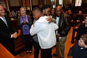 Charles Johnson left, hugs Kenny Johnson, 14, while adopting him at the National Adoption Day ceremony at the Jefferson County Courthouse on Friday. Charles, a coach at Vincent Middle School, was formerly a teacher to Kenny. Photo taken Friday, 11/16/18