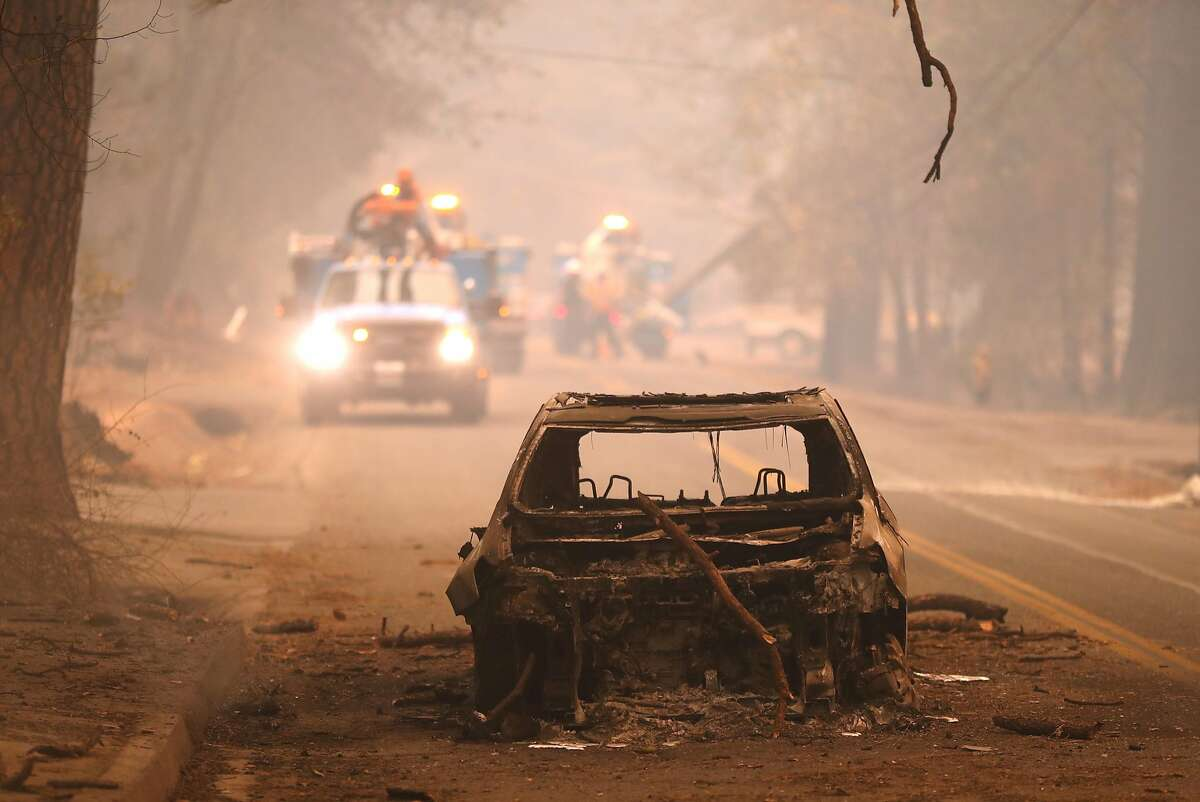 As PG&E crews work behind it, a burned out car sits in Bille Road after Camp Fire in Paradise, Calif. on Friday, November 9, 2018.