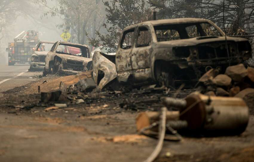 Charred cars and power lines sits along Pearson Road in Paradise, Calif. Wednesday, Nov. 14, 2018 after the Camp Fire ripped through the entire town.